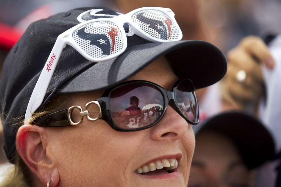 Beth Barnes smiles as defensive end J.J. Watt, reflected in her sunglasses, signs an autograph after practice. Photo: Brett Coomer, Chronicle