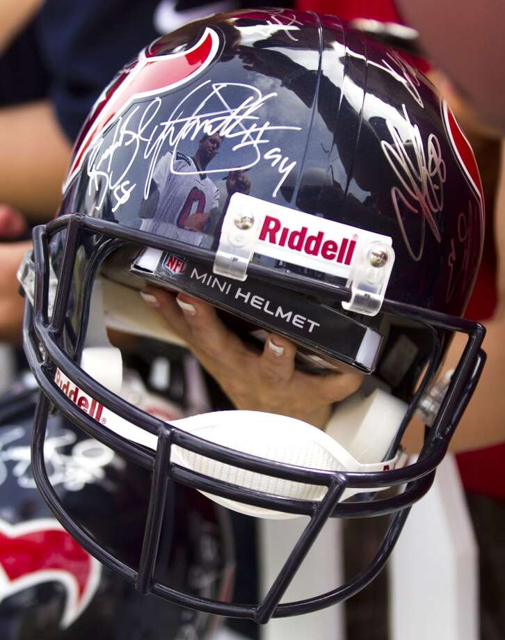 Punter Shane Lechler is reflected in an autographed Texans helmet at the end of practice. Photo: Brett Coomer, Chronicle