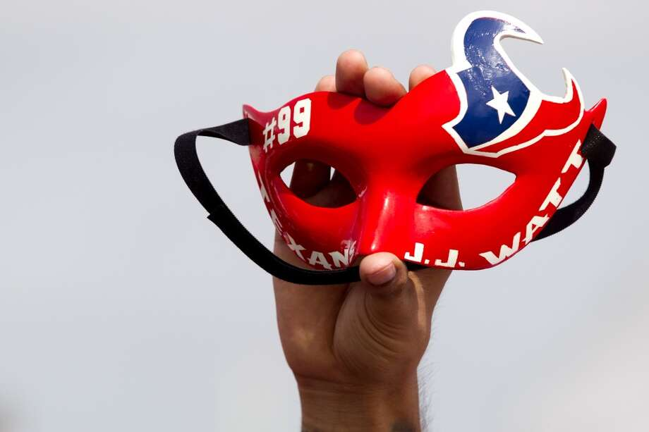 A fan holds up a Texans-themed mask. Photo: Brett Coomer, Chronicle