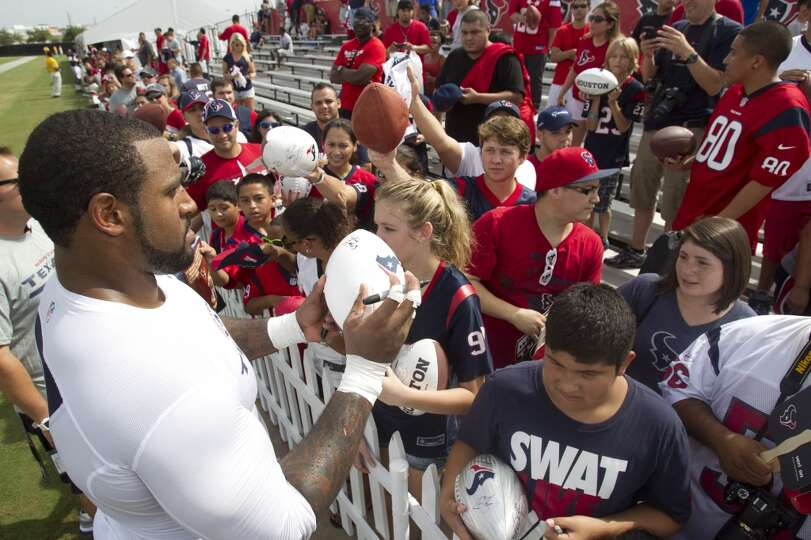Tackle Duane Brown, left, signs autographs after practice.