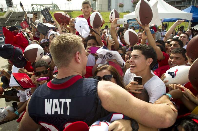Defensive end J.J. Watt embraces a group of fans as he signs autographs after practice.
