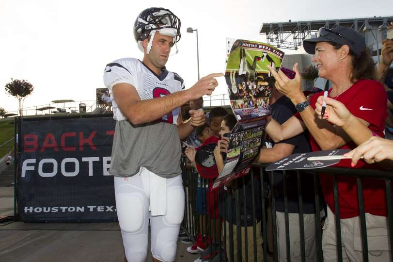 Quarterback Matt Schaub signs autographs on his way to practice.