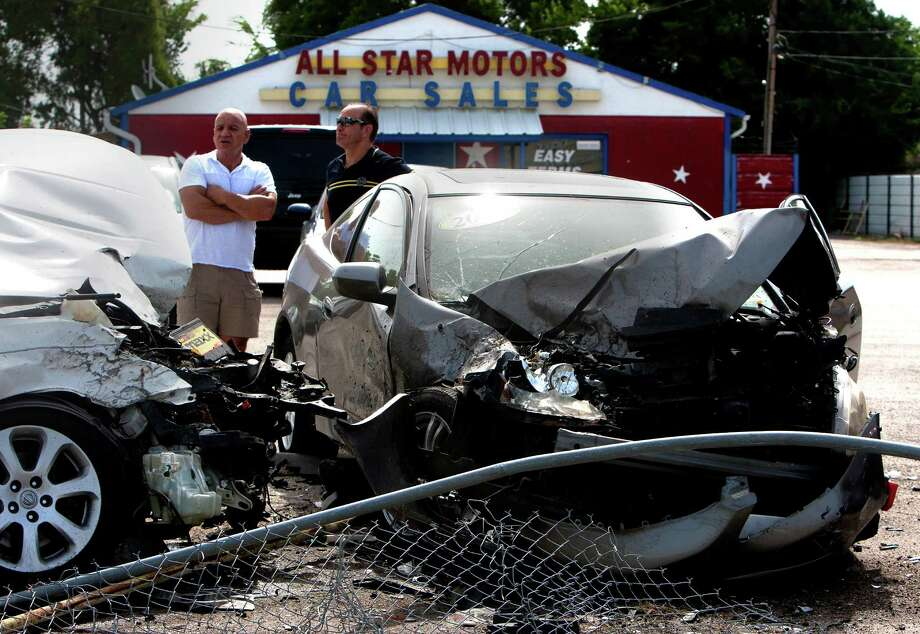 Friend Ted Zahra, left, and owner of All Star Motors, Frank Obeid, right, look at the damage done to used inventory after a driver crashed into the lot damaging several cars in the 1900 block of  South Highway 6, Tuesday, July 30, 2013, in Houston. The crash occurred around 3:15 a.m. when the driver of a U-Haul truck crossed over the oncoming lane and into the dealership damaging eight vehicles. Photo: Cody Duty, Houston Chronicle / © 2013 Houston Chronicle