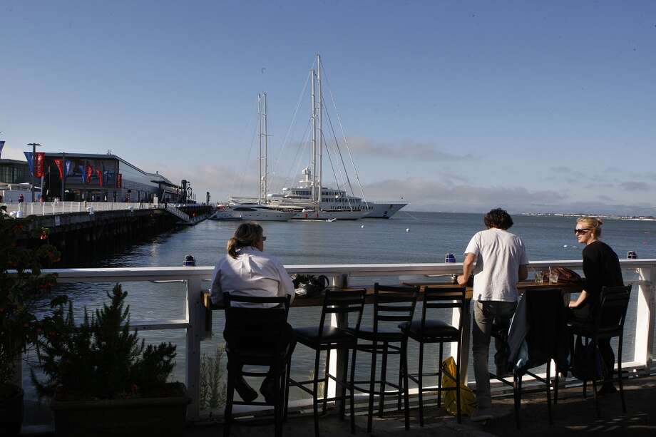 Patrons look out toward Pier 27 from the patio dining area of Pier 23. Photo: Liz Hafalia, The Chronicle