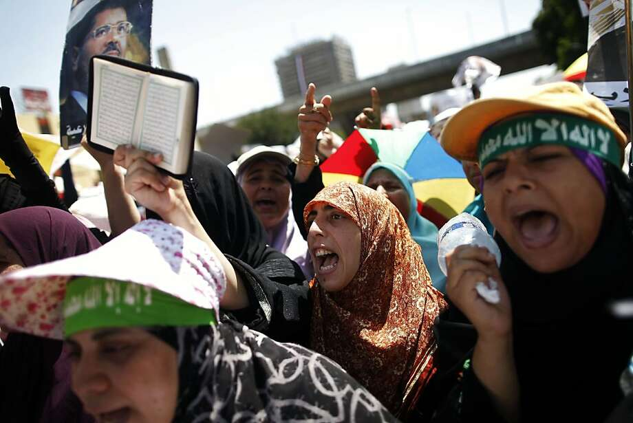 "An Egyptian supporter of deposed president Mohamed Morsi raises a Koran shouting slogans during a demonstration against the government in Cairo on July 30, 2013. EU foreign policy chief Catherine Ashton met Egypt's ousted president on July 30, 2013, saying he was ""well,"" but the country's political crisis seemed no closer to resolution despite her efforts.    AFP PHOTO/MAHMOUD KHALEDMAHMOUD KHALED/AFP/Getty Images Photo: Mahmoud Khaled, AFP/Getty Images"