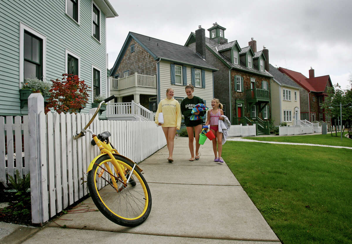 Kelsey Mendenhall, 13, (from left), Stefania (cq) Ghilarducci, 13 and Ivy Mendenhall, 11 and Kelsey's sister, all of Seattle, head to the beach from the house they rented at Seabrook in Pacific Beach, Wash. on Wednesday, August 20, 2008. Loaner bicycles are available to owners and guests of the new beach town.