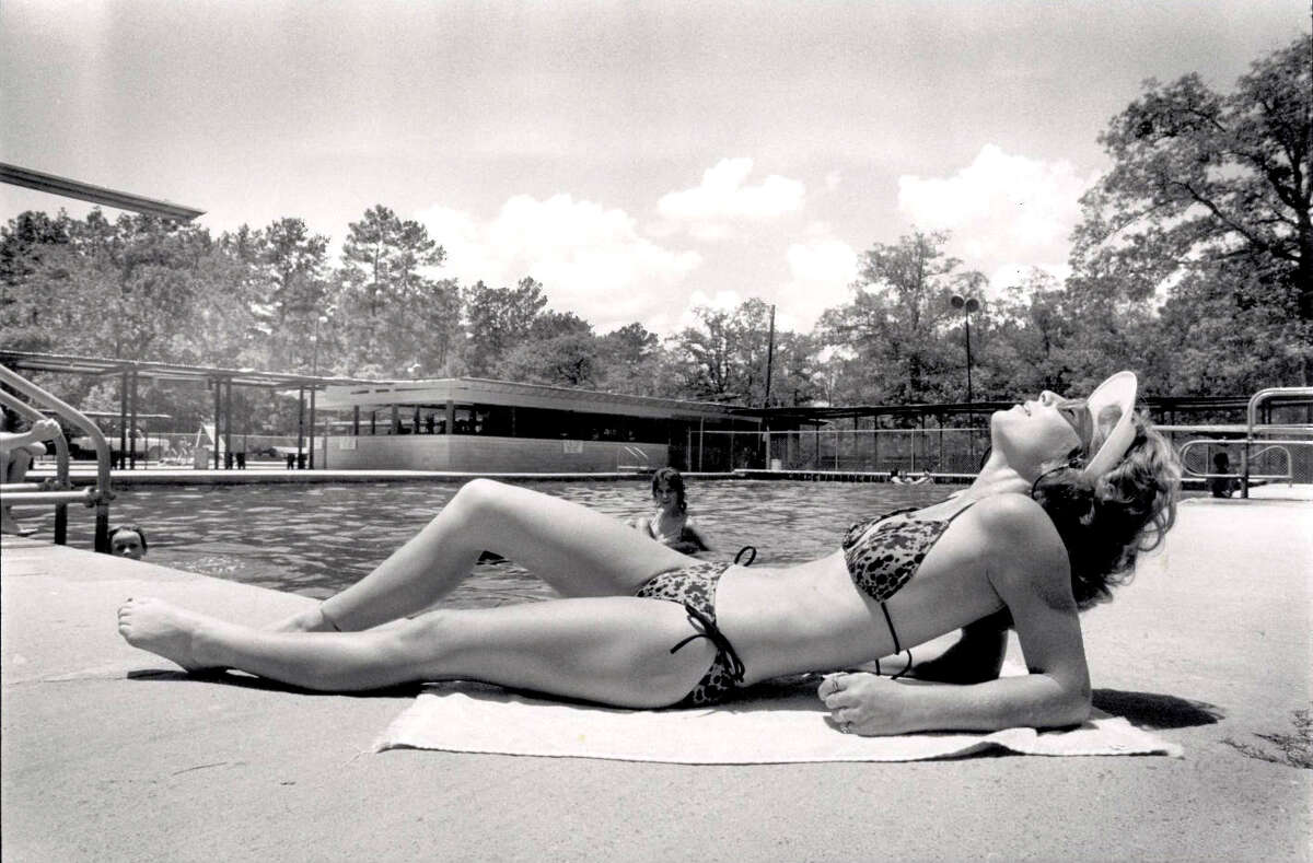 Kim Stockholm of Kountze enjoys the recent warm temperatures as she soaks up some rays at the Honey Island Swimming Pool. The pool is fed from an artesian well dug in 1912. Beaumont Enterprise file photo.