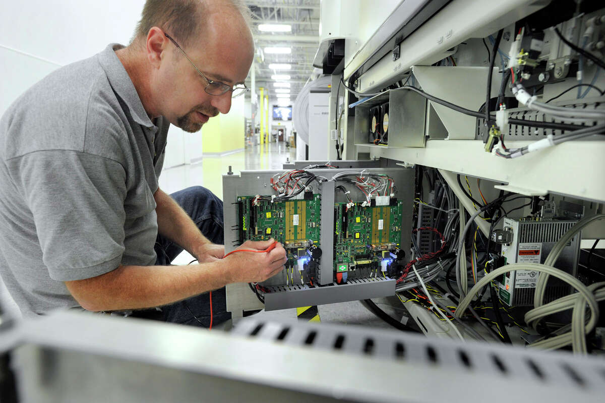 An electrical engineer at Pitney Bowes works on one of the company's products in the Global Technology Center. Pitney Bowes is selling its management services unit to Apollo Global Management for $400 million as the Stamford-based firm focuses on core operations.