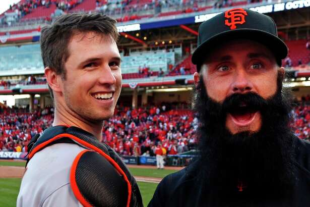 San Francisco Giants' Buster Posey celebrates with pitcher Brian Wilson after they defeated the Cincinnati Reds 6-4 in Game 5 of the National League division baseball series, Thursday, Oct. 11, 2012, in Cincinnati.  The Giants won the final three games, all in Cincinnati, and advanced to the NL championship series.