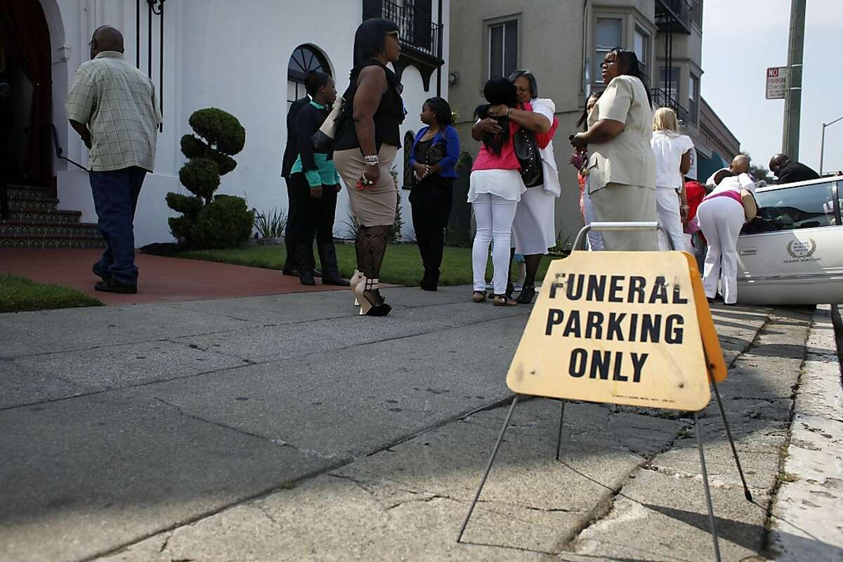 Family and friends comfort each other as they arrive for the funeral of Alaysha Carradine, Tuesday July 30, 2013, at the McNary-Williams-Jackson Mortuary in Oakland, Calif. Alaysha, 8, was shot and killed when a gunman opened fire through the door of a friend's house.