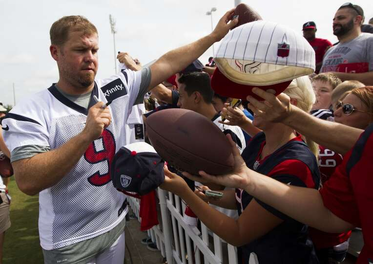 Punter Shane Lechler signs autographs for fans at the the conclusion of practice.