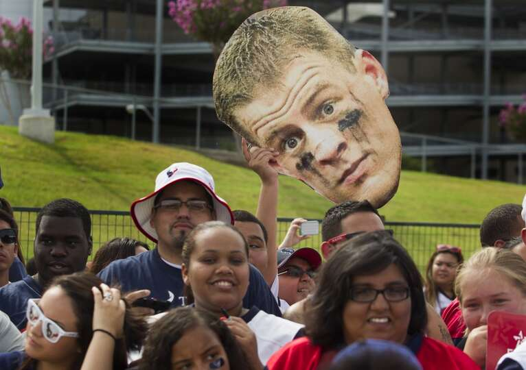 Fans hold up a J. J. Watt cut out.
