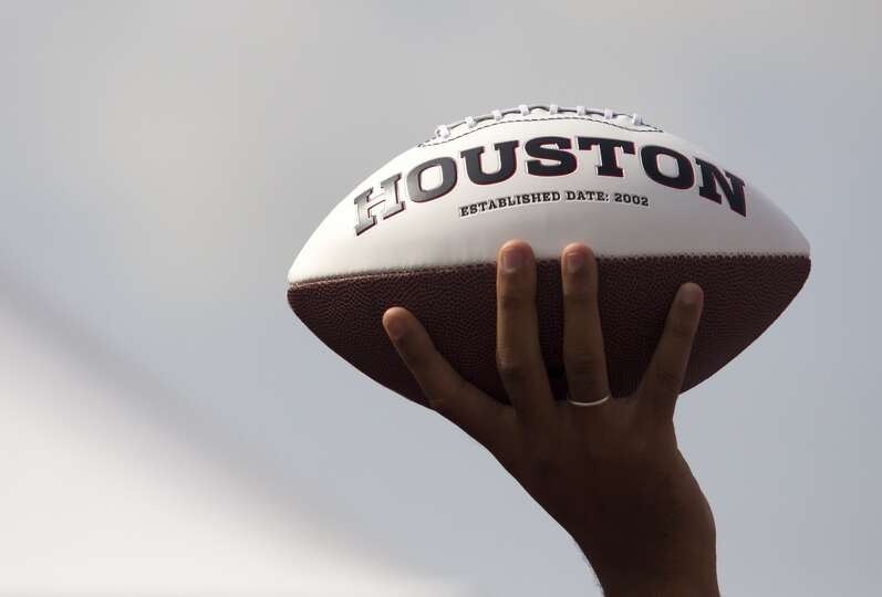 A fan holds up a Texans football.