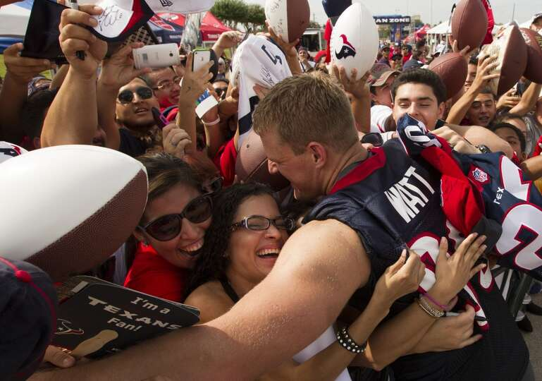 J. J. Watt hugs fans as he leaves the field.