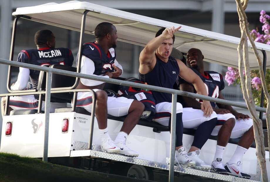 Brian Cushing signals fans as he rides a cart to practice with Brice McCain, back, Kareem Jackson, left, and Johnathan Joseph. Photo: J. Patric Schneider, For The Chronicle