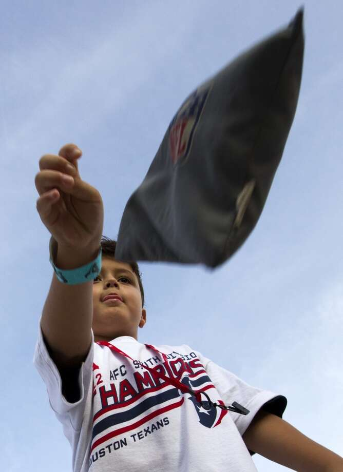 Jace Garza, 6, throws a bean bag in the fan area. Photo: J. Patric Schneider, For The Chronicle