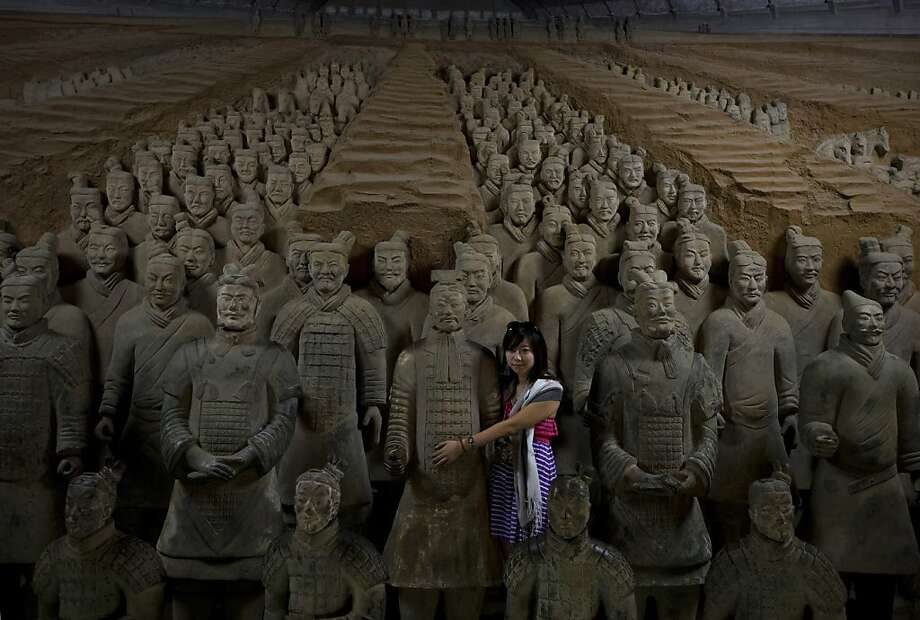 A woman hugs a terracotta warrior replicas as she post for a souvenir photo at the Museum of Qin Terracotta Warriors and Horses in Xi'an, in central China's Shaanxi province Tuesday, July 30, 2013. Thousands of terracotta soldiers that were buried in the tomb of the Emperor Qin Shihuang, who ruled China between 221-210 B.C., are displayed in Xi'an. (AP Photo/Andy Wong) Photo: Andy Wong, Associated Press