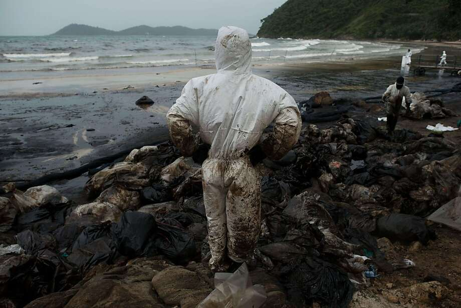 Thai slick:Royal Thai Navy personnel clean up Ao Phrao beach after a major oil spill from a ruptured pipeline coated the popular tourist spot on the island of Ko Samet. Photo: Nicolas Asfouri, AFP/Getty Images