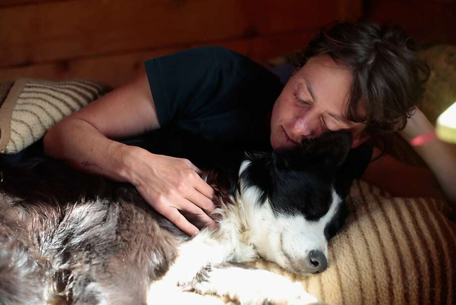 Summer shepherd: Katharina Brueggebors relaxes with her sheepdog, Nelly, inside her cottage at the Sesvenna Alpe near Malles Venosta/Mals, Italy. During the day, she watches over a herd of 300 cattle. Farmers in valley villages commission herders to bring the animals up to mountain plateaus to spend the summer feeding on the grass-rich meadows. Photo: Johannes Simon, Getty Images