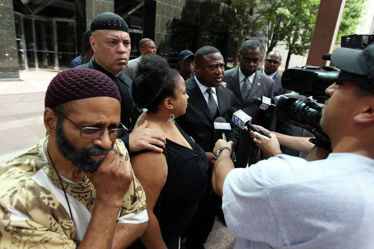 Quanell X speaks to the media surrounded by Deloid Parker, Kofi Taharka, with the National Black United Front, Krystal Muhammad, with the New Black Panther Party, and others after their meeting with Dept. of Justice Official Kenneth Madgison at the Wells Fargo Building, Tuesday, July 30, 2013, in Houston. ( Karen Warren / Houston Chronicle )