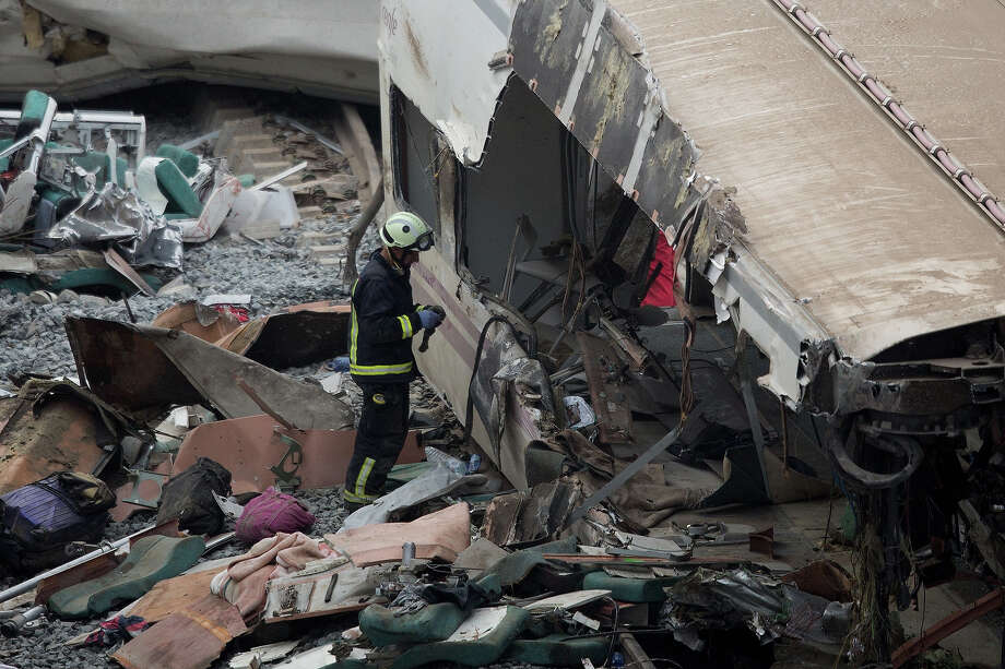 A firefighter works at the scene of a train crash that killed at least 77 people on July 25, 2013 at Angrois near Santiago de Compostela, Spain. The crash occurred on Wednesday at 8.40pm as the train approached the north-western Spanish city of Santiago de Compostela, with 247 passengers on board.  At least 77 people have died and a further 131 have been reported injured. The crash occurred on the eve of Santiago de Compostela's main religious festival. Photo: Pablo Blazquez Dominguez, Getty Images / 2013 Getty Images