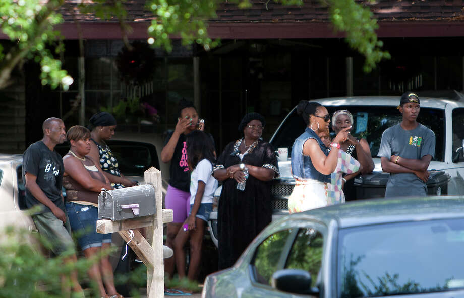 Neighbors gather to watch the police proceedings Friday at the group home on Whitecastle Lane.  Some said  they had not noticed anything out of the ordinary at the home. Photo: Cody Duty, Staff / © 2013 Houston Chronicle