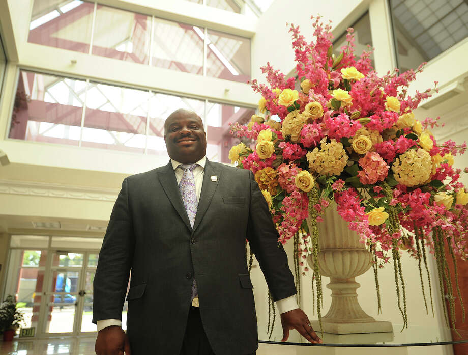 The Rev. Kenneth Moales, Jr. stands beside a custom artificial flower arrangement ordered by his mother, inside the lobby of the Cathedral of the Holy Spirit, the church built by his father, at 790 Union Avenue in Bridgeport, Conn. on Tuesday, July 30, 2013. Photo: Brian A. Pounds / Connecticut Post