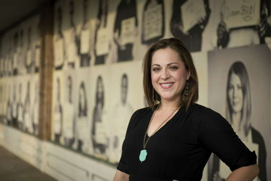 "Sarah Brooke Lyons stands in front of her ""1005 Faces"" installation. The black-and-white photos force a different focus from the viewer, Lyons says. Photo: Darren Abate / For The Express-News"