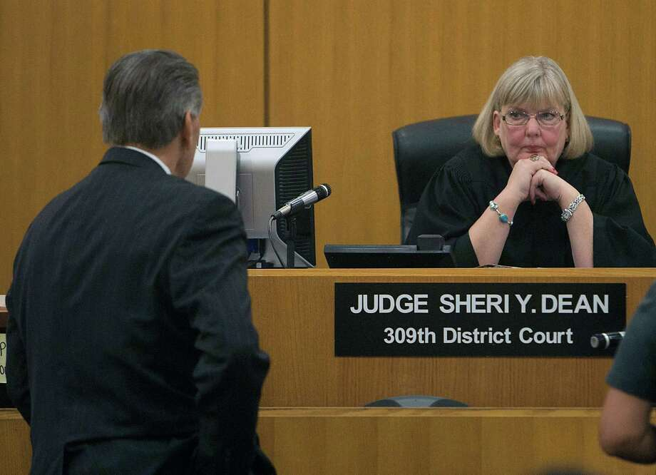 John Nichols left, an attorney for Michael Brown, Judge Sheri Y. Dean right, during a hearing on a contempt-of-court order for former hand surgeon Michael Brown in the 309th Family Court, Tuesday, July 30, 2013, in Houston. Depending upon the outcome of this hearing, he could be sent back to jail. This contempt finding was  for failing to let a court official inspect his house in Miami Beach. Photo: James Nielsen, Houston Chronicle / © 2013  Houston Chronicle
