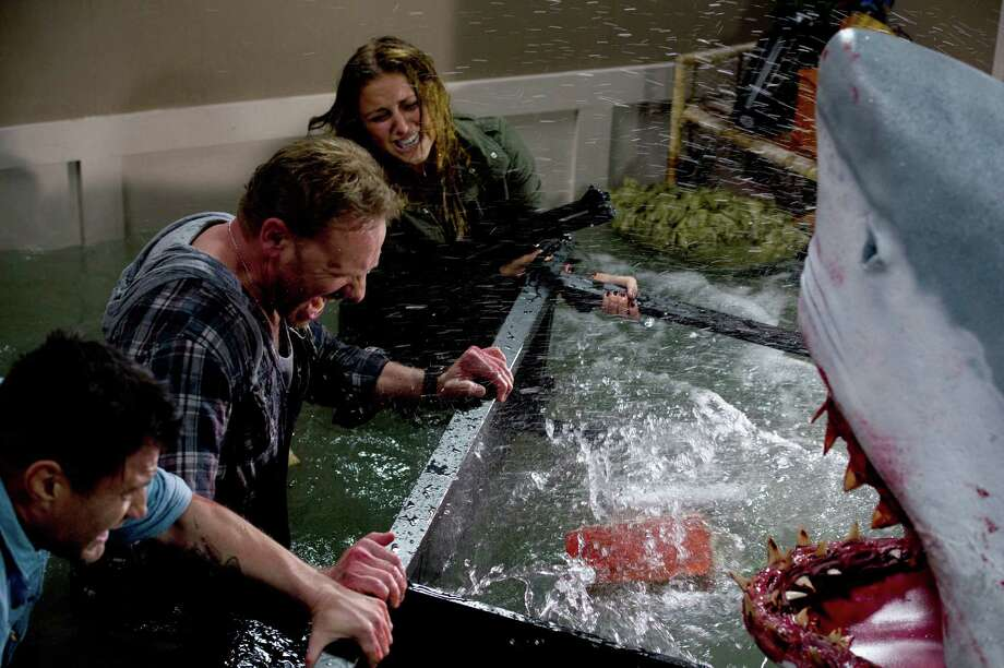 "Ian Ziering (middle), straying far from a 90210 ZIP code, and Cassie Scerbo (right) battle a shark in the Syfy film ""Sharknado,"" which has become an instant camp classic. Photo: Associated Press / Syfy"