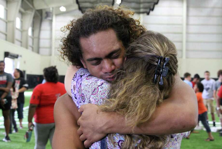 Fua Sapoi, 18, hugs a teacher during a memorial Tuesday, July 30, 2013 in Euless, Texas, dedicated to three teenagers who died Monday in a New Mexico car crash, two of whom were Sapoi's former teammates at Trinity High School in Euless. Texas A&M said Tuesday that redshirt freshman Polo Manukainiu and a friend who was joining the Utah football team this fall were among the three killed in the single-car rollover crash in the high desert of northern New Mexico, stunning both schools just days before fall practices begin.  (AP Photo/Uriel J. Garcia) Photo: Uriel J. Garcia, Associated Press / AP