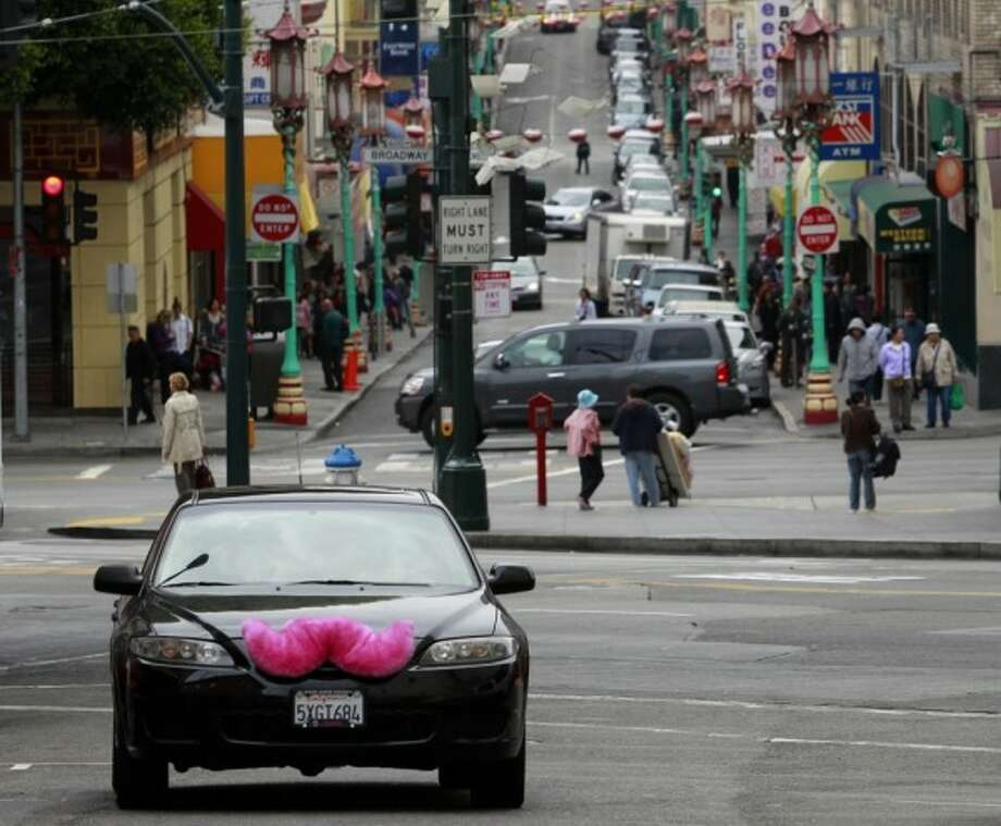 A Lyft car drives through Chinatown. Lyft and UberX drivers have been cited and arrested for picking up and dropping off rides at SFO.