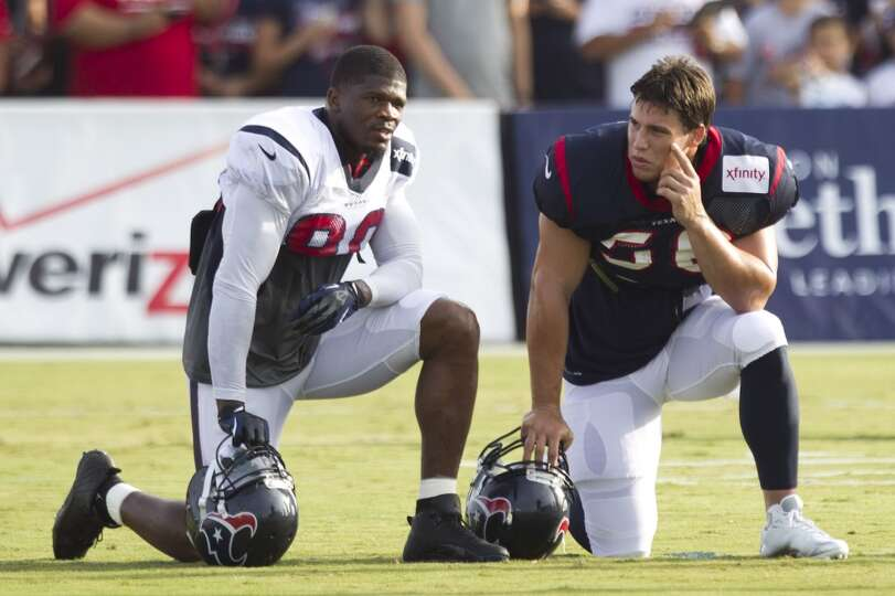 Wide receiver Andre Johnson (80) and inside linebacker Brian Cushing (56) take a break between drill