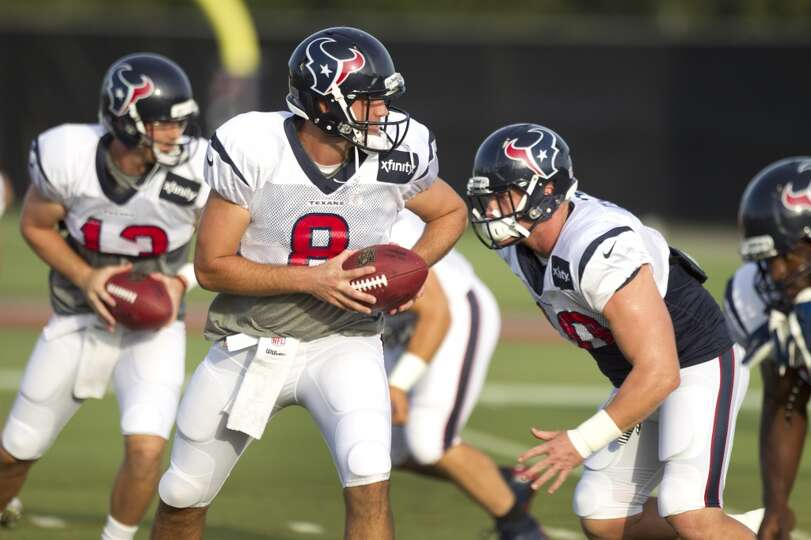 Quarterbacks Matt Schaub (8) and T.J. Yates (13) run through a handoff drill.