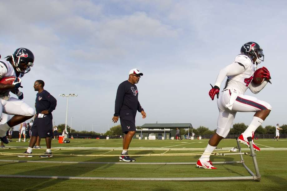 Running back Ben Tate, right, runs through an agility drill with running backs coach Chick Harris looking on. Photo: Brett Coomer, Chronicle