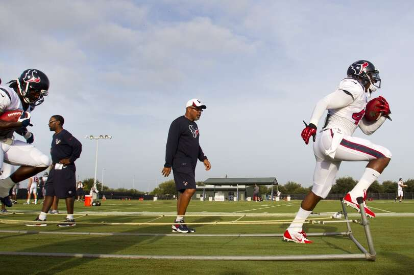 Running back Ben Tate, right, runs through an agility drill with running backs coach Chick Harris lo