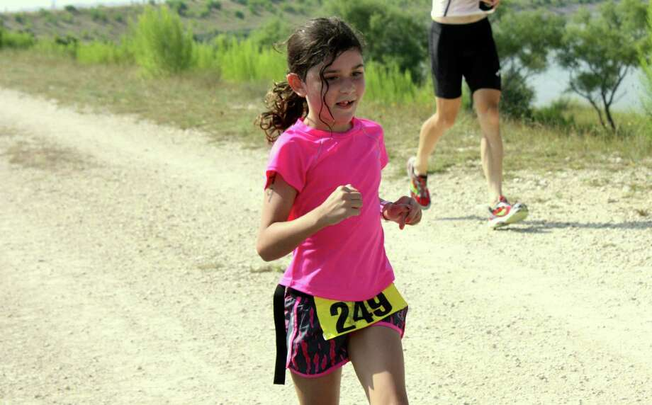Eight-year-old Sydney Meelbusch crosses the finish line at last Sunday's Tiny Texan Triathlon at Boerne City Lake. She was running a relay with her father, Brian Meelsbusch. Photo: Mike Reeder / For The Northwest Weekly