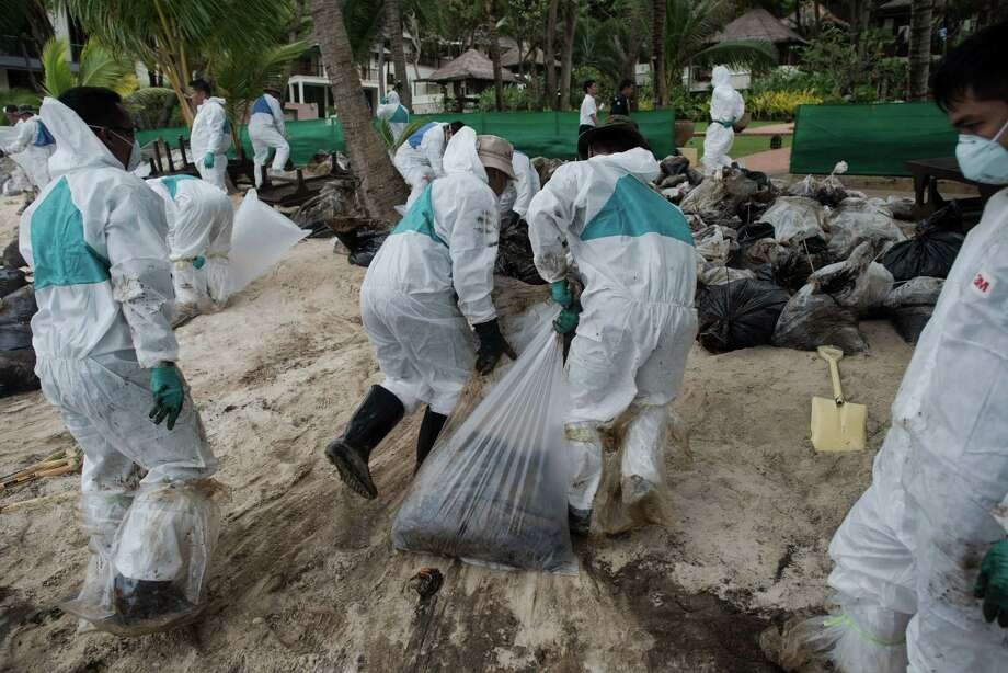 Royal Thai Navy personnel work to clean up from a major oil slick on Ao Phrao beach on the island of Ko Samet on July 30, 2013. Thai navy personnel battled to clean up the major oil slick which coated a beach on the popular tourist island in a national park after a pipeline leak. Photo: NICOLAS ASFOURI, AFP/Getty Images / AFP