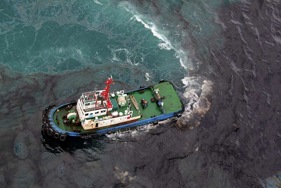 In this photo taken Saturday, July 27, 2013, a cleaning vessel clears the oil after about 50 tons of crude oil was leak from a pipe spilled into the sea off Rayong province, eastern Thailand. The oil spill that leaked from a pipeline, operated by a subsidiary of state-owned oil and gas company PTT Plc, has reached a popular tourist island in Thailand's eastern sea despite continuous attempts to clean it up over the weekend, officials said Monday. Photo: Associated Press / The Nation-Atchara