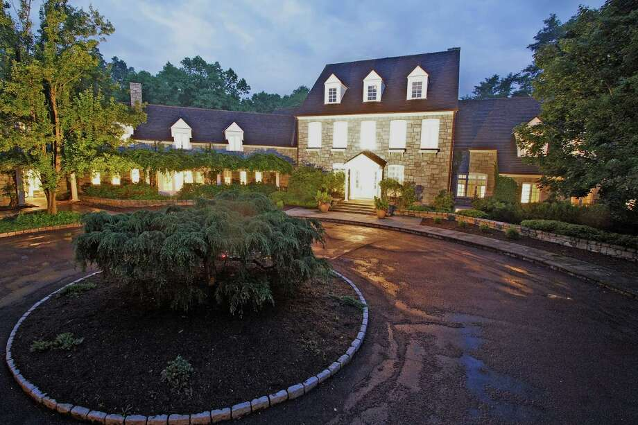A 13-acre Conyers Farm estate at 2 Cowdray Park Drive is ready to be auctioned off. Initial bids on the 11,000-square-foot, four-story colonial homethat features six bedrooms, seven full bathrooms, two powder rooms, four fireplaces, two half-bathrooms, a three-car garage, and a finished basement featuring a wine cellar and a recreation room with a wet bar, must be submitted by Aug. 20. Minimum bid? $4.6 milion. Photo: Contributed Photo / Greenwich Citizen
