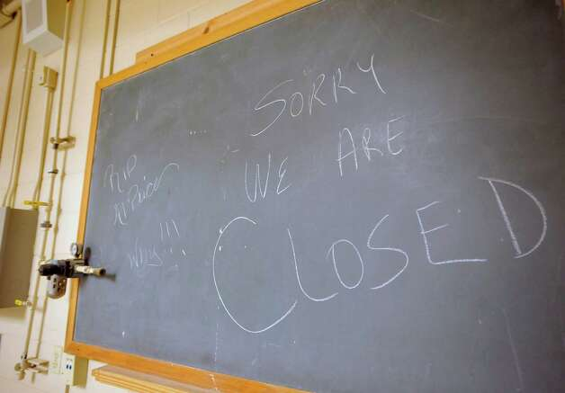 Inside the vocational building, as it was known, the wood shop's blackboard says i