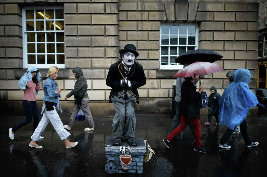 Members of the public, walk past a street entertainer on the Royal Mile on July 29, 2013 in Edinburgh, Scotland. The city is preparing ahead of the Edinburgh Fringe Festival which runs from the 2 -26 August and is one of the largest arts festivals in the world, dating back to 1947. The festival attracts thousands of performers from across the world to showcase their acts in Scotland's capital. Photo: Jeff J Mitchell, Getty Images / 2013 Getty Images