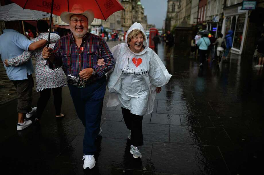 Members of the public shelter from the rain on the Royal Mile on July 29, 2013 in Edinburgh, Scotland. The city is preparing ahead of the Edinburgh Fringe Festival which runs from the 2 -26 August and is one of the largest arts festivals in the world, dating back to 1947. The festival attracts thousands of performers from across the world to showcase their acts in Scotland's capital. Photo: Jeff J Mitchell, Getty Images / 2013 Getty Images