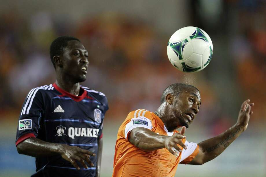 Dynamo left back Corey Ashe, right, is a two-time MLS All-Star who likely will receive an invitation to join the U.S. national team camp in January to prepare for the World Cup. Photo: Karen Warren, Staff / © 2013 Houston Chronicle