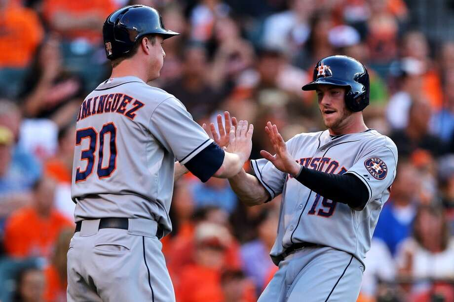 Astros teammates Robbie Grossman and Matt Dominguez congratulate each other after they both scored off a hit by teammate Jose Altuve in the third inning against the Orioles. Photo: Patrick Smith, Getty Images