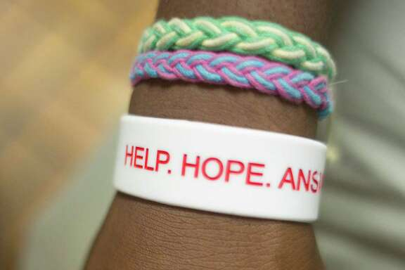 "Angelo, 18, wears a wrist band that reads ""Help, Hope, Answers"" at Covenant House."