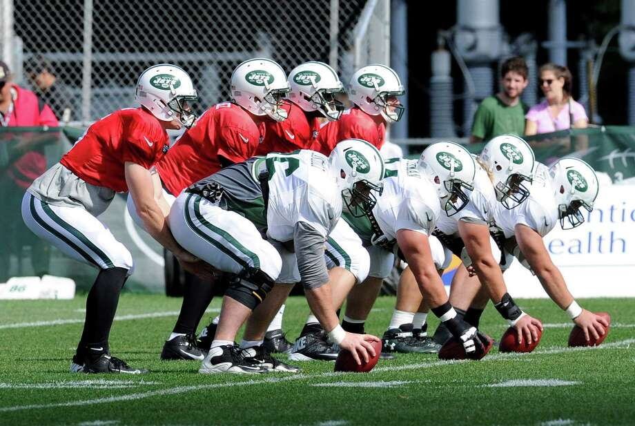 CORRECTS QUARTERBACKS AT END  TO MATT SIMMS AT LEFT GREG MCELROY FAR RIGHT-From left, New York Jets quarterbacks Matt Simms, Mark Sanchez, Geno Smith and Greg McElroy take snaps at their NFL football training camp Monday, July 29, 2013, in Cortland, N.Y. (AP Photo/Bill Kostroun) ORG XMIT: NYBK103 Photo: Bill Kostroun / FR51951 AP