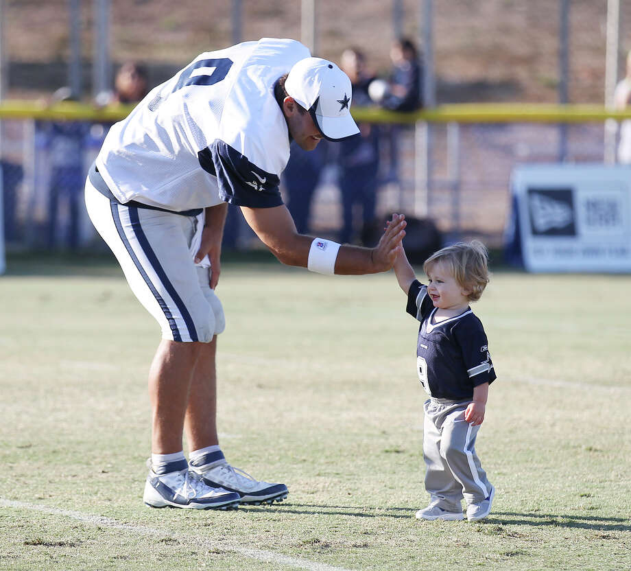 Quarterback Tony Romo offers a high five to his nearly 16-month-old son, Hawkins, after the afternoon session of the 2013 Dallas Cowboys training camp on Tuesday, July 30, 2013 in Oxnard. Photo: Kin Man Hui, San Antonio Express-News / ©2013 San Antonio Express-News