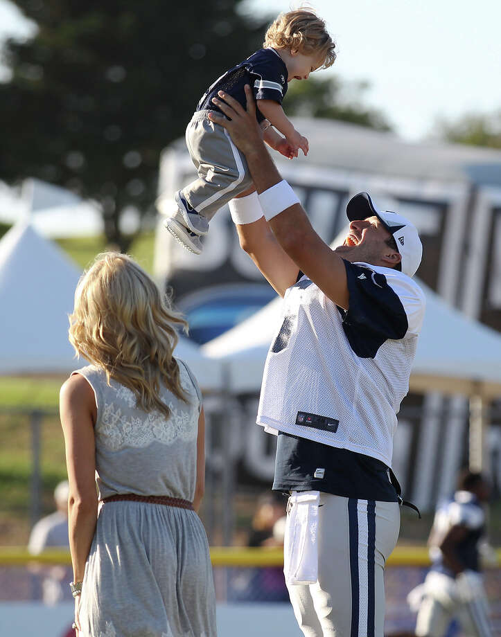 Quarterback Tony Romo lifts his son, Hawkins, into the air as Romo's wife Candice watches after the afternoon session of the 2013 Dallas Cowboys training camp on Tuesday, July 30, 2013 in Oxnard. Photo: Kin Man Hui, San Antonio Express-News / ©2013 San Antonio Express-News