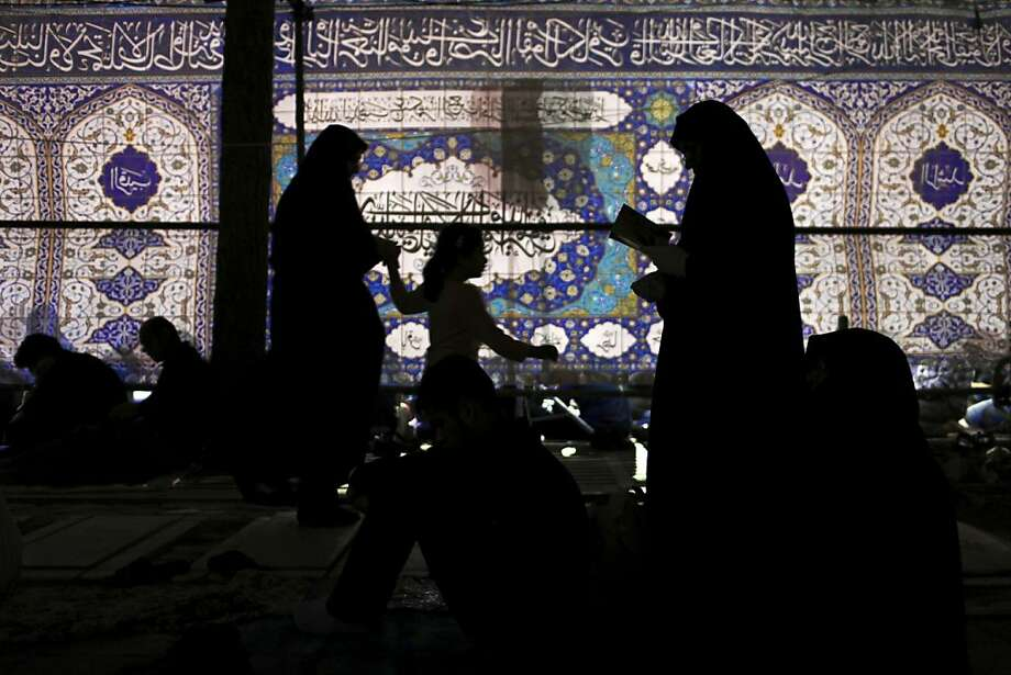 Iranians attend a religious ceremony marking Imam Ali's death at the Behesht-e-Zahra cemetery, just outside Tehran, Iran, early Tuesday, July 30, 2013. Iranians commemorate the anniversary of Imam Ali's death, the first Imam of Shia Muslims on the 21st day of Ramadan. (AP Photo/Ebrahim Noroozi) Photo: Ebrahim Noroozi, Associated Press